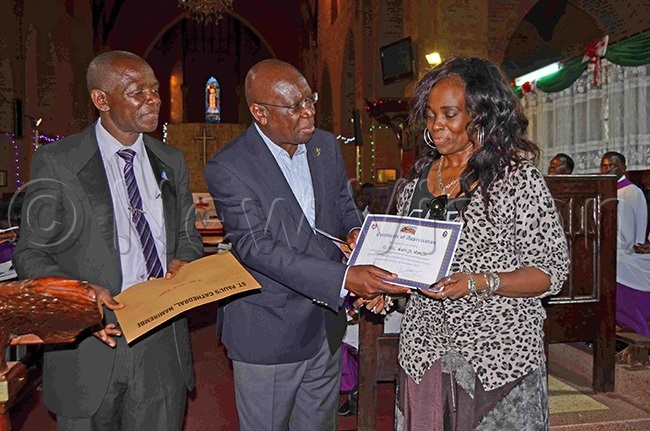 he hairman of amirembe athedral hoir r srael uutu centre handing over a meritorious certificate to ose anteza sibambi right in appreciation of her immense support to the choir over the years