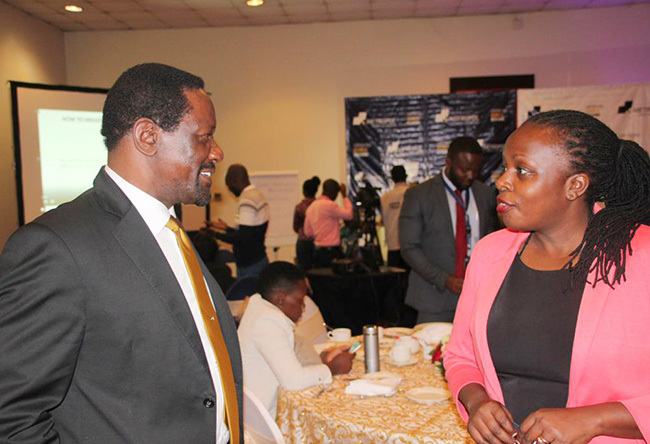 mukoko interacting with a colleague at the breakfast meeting
