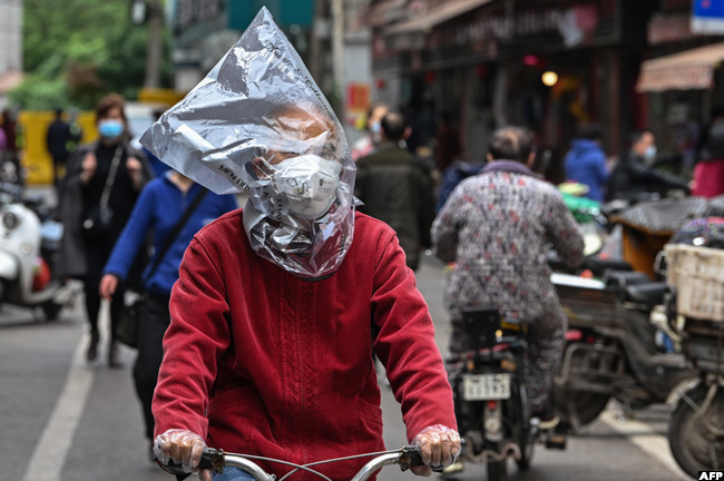 his man riding a bicycle on a street in uhan hina is not taking any chances
