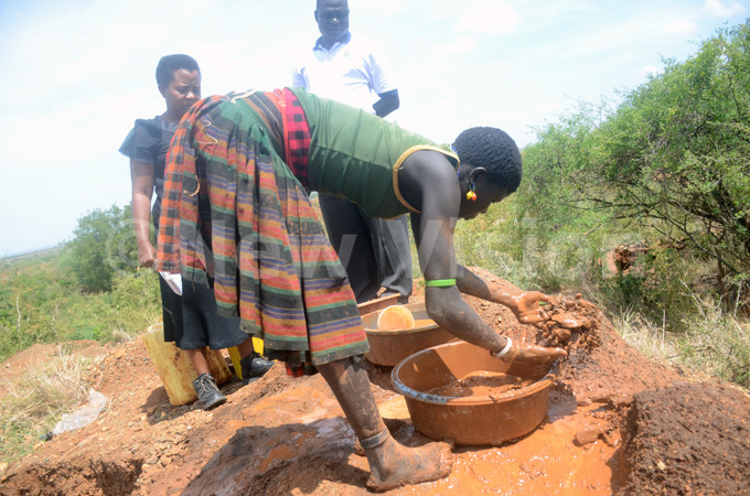 girl extracting gold from ore using water in a basin in oroto district in aramoja