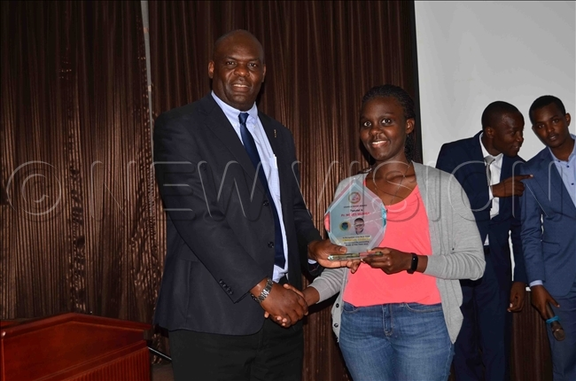 hibita handing over an accolade to orah aguma the daughter of author oses ukisa who was the overall winner of the awards