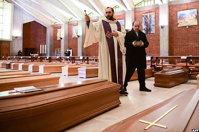 riest on arcello gives a blessing to the coffins of deceased people inside the church of an iuseppe in eriate taly