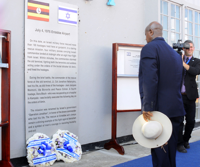 resident useveni stands in front of the commemorative plaque  hoto