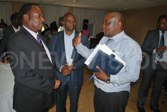 lbert asozi ule the principal nutritionist at the health ministry chatting with r ohn sekamatte the executive member from ational planning uthority left ooking on is a participants center