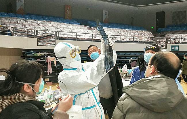 a onggang  in a protective suit looking at a  image at uchang makeshift hospital in uhan in hinas central ubei province