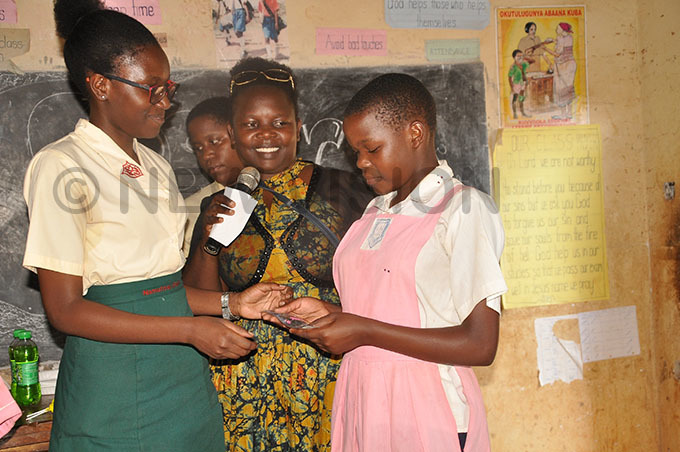 ansubuga middle and one of her learners left rewarding a young female learner at itankya rimary chool who excelled in  after she was supported to stay in school hoto by ichard etaya