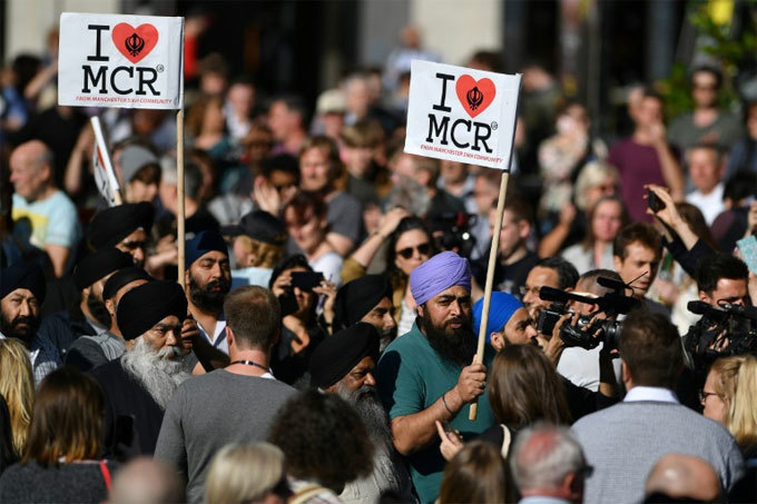 eople from anchester ikh ommunity carry  love  banners as they arrive to attend a vigil in lbert quare in anchester on ay 23 2017 in solidarity with those killed an injured in the ay 22 terror attack at the riana rande concert  en