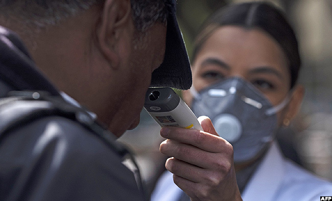 nurse checks a mans temperature at the entrance of ijuanas eneral ospital in ijuana exico