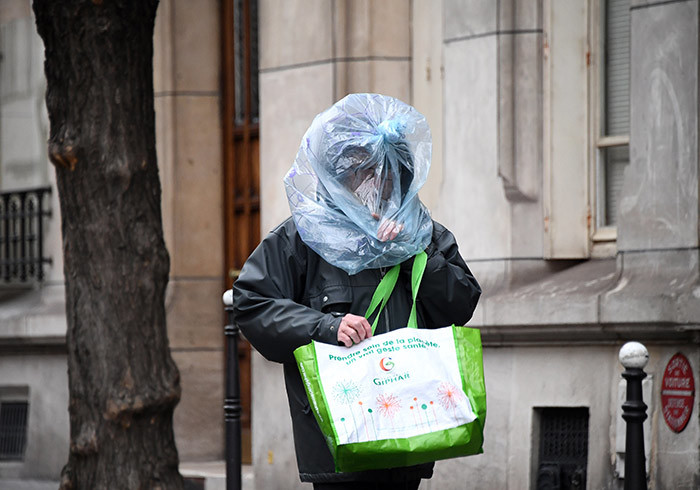man protect his face with a plastic bag as he walks in the street in aris on arch 21 2020 as a strick lockdown comes into in effect to stop the spread of the 19 in the country  rench resident asked people to stay at home to avoid the spreading the ovid19 saying only necessary trips would be allowed and violations would be punished he country has already shut cafes restaurants schools and universities and urged people to limit their movementnonessential public places including restaurants and cafes hoto by