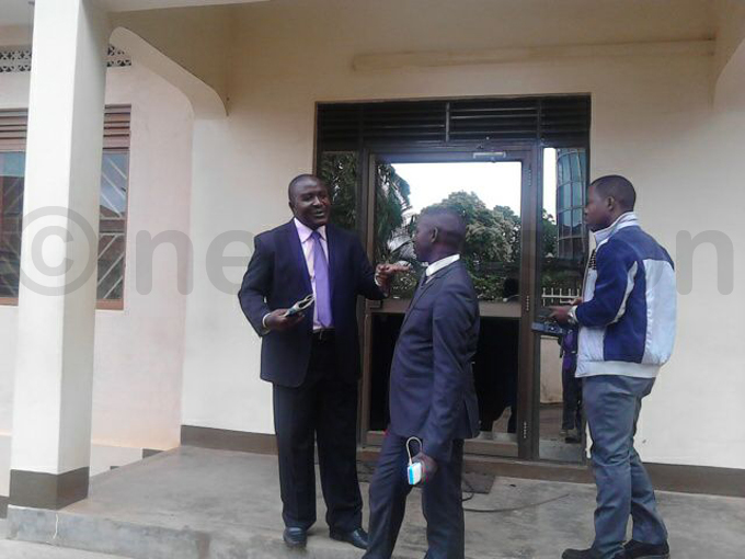 babazi  chats with a colleague outside the offices hoto by uliet asirye