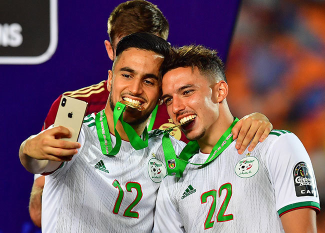 lgerias forward dam unas and lgerias midfielder smail ennacer celebrate after winning the 2019 frica up of ations