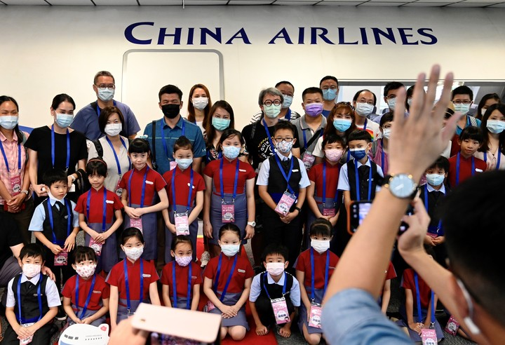 A parent (foreground R) takes a group photo of flight attendants and participating children during a 'fly to nowhere' event at the China Airlines' campus in Taoyuan City. AFP photo