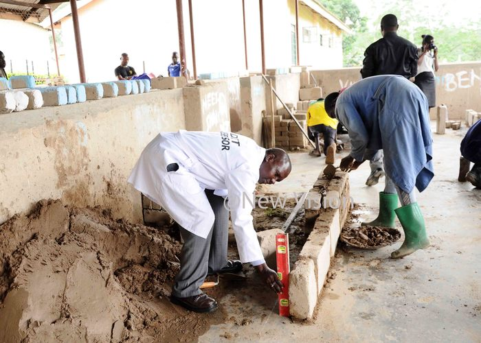 ackson osinghi the assessor assessing senior three student of ew orizon secondary and ocational schools in brick laying skills his was at during the implementation of   the dual curriculum in secondary schools