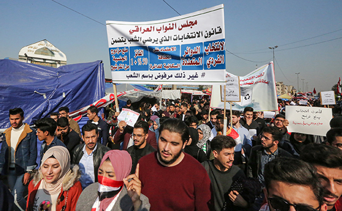 rotesters chant slogans as they march with protest signs and national flags during an antigovernment demonstration in the raqi capital aghdads central ahrir quare on ecember 22 2019 hoto by