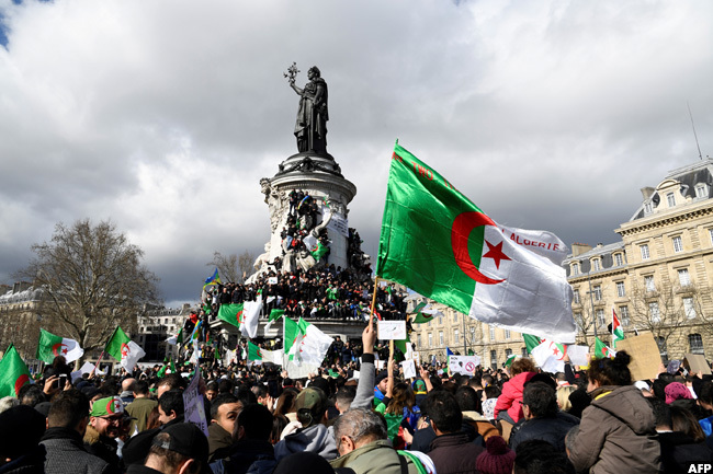 emonstrators shouted slogans as they marched with placards and flags during a rally at lace de la epublique in aris in support of the ongoing protests in lgeria against the presidents bid for a fifth term in power