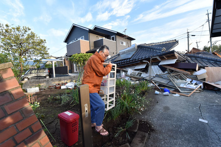 man removes furniture in front of his collapsed house in ashiki umamoto prefecture on pril 16 2016