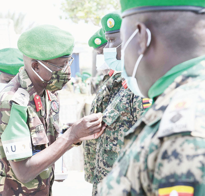 Maj. Gen. Owinow pins a medal on a Ugandan military officer