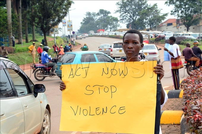 young woman from the afer ities roject of lan nternational ganda displays messages to motorists and cyclists along ampewo oundabout in ampala as part of the activities to mark the launch of the 16 ays of ctivism ampaign against gende rbased violence hoto by ddie sejjoba