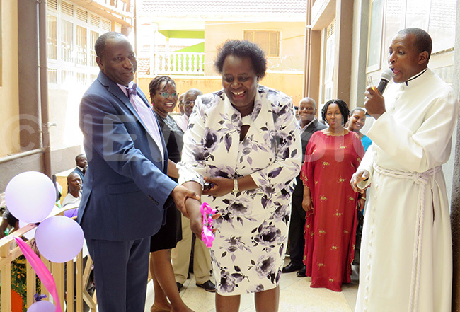eft to right rof harles bingira and his wife ydia bingira cut the tape as ev anon vatt ugarura cheers them at the launch of their newly built hospital hoto by arim sozi