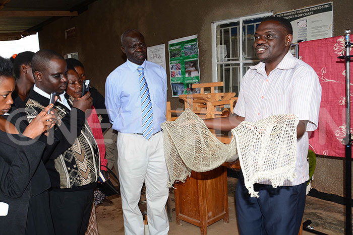 trainer atrick emambo shows a silk cloth to rederick uyambasi commissioner entomology with inistry of griculture