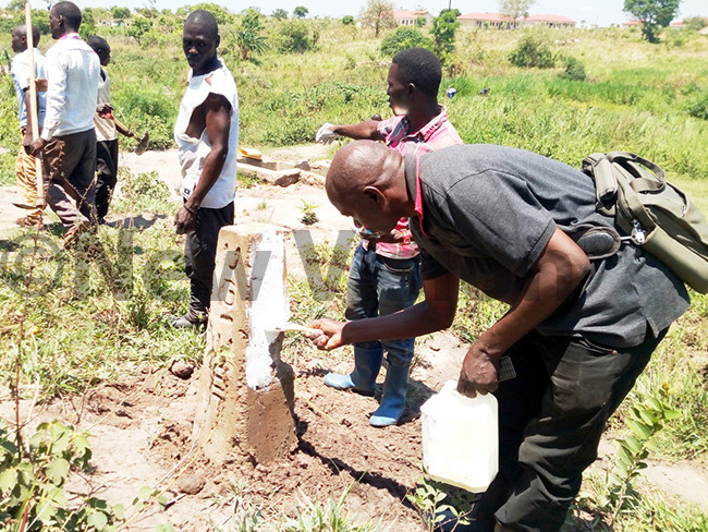 fai illustrating to the youth how to paint a pillar in muru during the demarcation of wee stream hoto by rnest umwesige