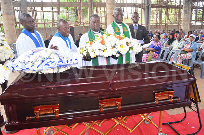 ev illiam sekitooleko secondleft ev braham ubega isaakye right and some layreaders laying a wreath on the casket on behalf of ateete nglican artyrs hurch