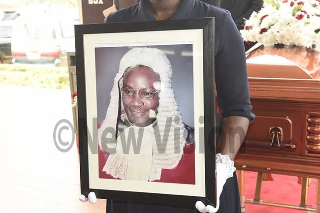 ormer udge ohn sekookos portrait is held by an official of  lus uneral ervice at t uke tinda ctober17 2019 hoto by ennedy ryema