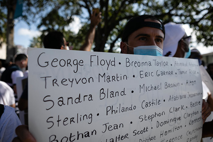 protestor holds a sign with the name of victims of police brutality during a rally in oral ables lorida on ay 30 2020 in response to the recent death of eorge loyd an unarmed black man who died while while being arrested and pinned to the ground by the knee of a inneapolis police officer hoto by va arie