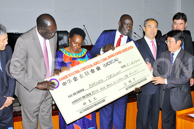 he  inister for elief isaster reparedness and efugees ilary nek inister of eneral uties ary aroro kurut tate inster for elief and isaster reparedness usa cweru and the hinese mbassador heng huqiang receiving at dummy cheque of sh12m from r eff in a representative of the hinese industrial  commercial agricultural mining ganda association