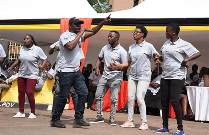 oses upercharger subuga puting on a cap with other teenagers who were born with  performing during the launch of 2020 ganda populationbased  mpact ssesment   at the inistry of health head offices in ampala