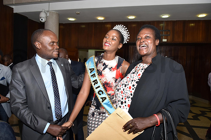s eogratius iyingi left and eronica sala itchetero right share a light moment with iss orld frica uinn benakyo at arliament after a motion was passed to recognise her efforts in the iss orld pageant hoto by iriam amutebi