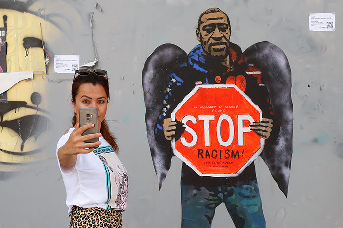 woman takes a selfie picture posing next to a street poster artwork by talian urban artist alvatore enintende aka  depicting eorge loyd with angel wings and holding a stop traffic sign against racism in a street of arcelona on ay 31 2020 hoto by