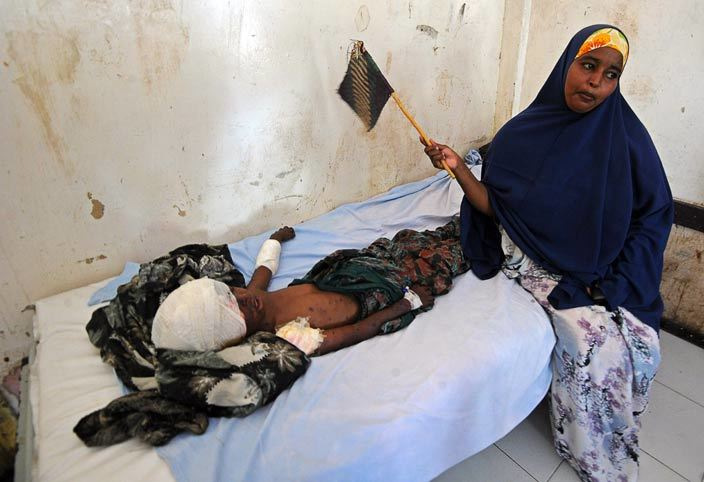 mother stands by her child laying in a bed at edina hospital on ebruary 27 2016 in ogadishu the day after the attack on  hotel  t least 14 people were killed on ebruary 26 as twin blasts and gunfire rocked a hotel and neighbouring park in central ogadishu police said in an attack claimed by the laedalinked hebab militants