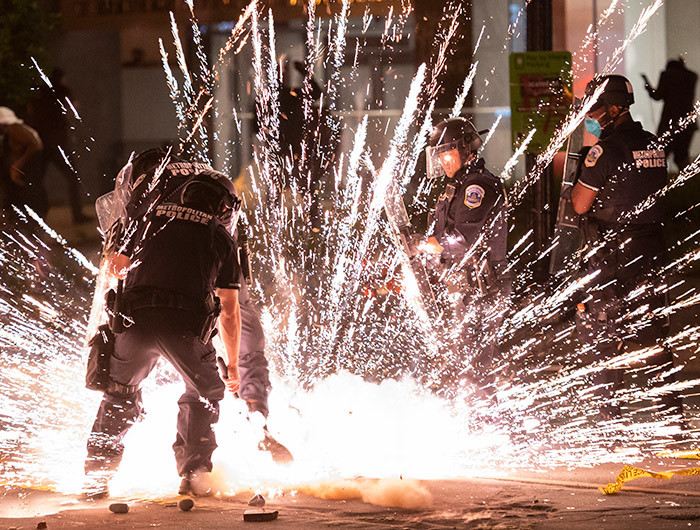 firecracker thrown by protesters explodes under police one block from the hite ouse on ay 30 2020 in ashington  during a protest over the death of eorge loyd an unarmed black man who died after a inneapolis police officer kneeled on his neck for several minutes  hoto by