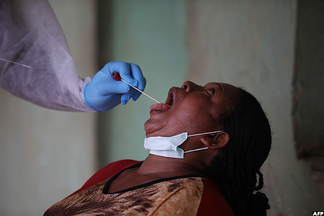 health worker takes a swab from a woman during a community coronavirus testing campaign in buja igeria