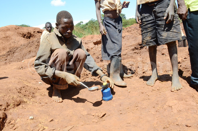 man extracting mercury from a piece of gold by heating it up using a gas stove in ugiri district