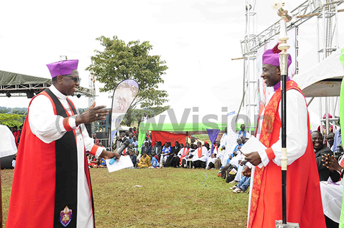 eft is rchbishop tanley tagali welcoming his successor ishop tephen azimba ugalu at the celebrations of the late rchbishop ames annington at yando in ayuge district