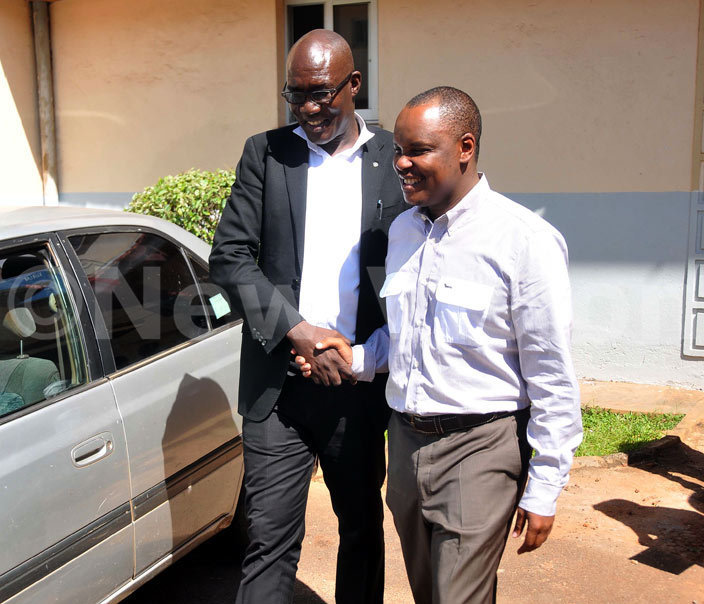 awyer ob asango right shakes hands with his lawyer arshal lenyo soon after he was granted bail asango was charged with urt lerk ilton utegeya for conspiring to forge a judicial document in order to steal pension cash amounting to sh154b