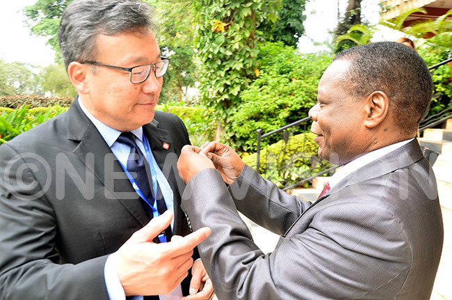 he hairperson of the nternational anitation treatment ystem project im un left looks on as the xecutive irector of ganda ational ureau of tandard  r en anyindo puts a badge on his coat