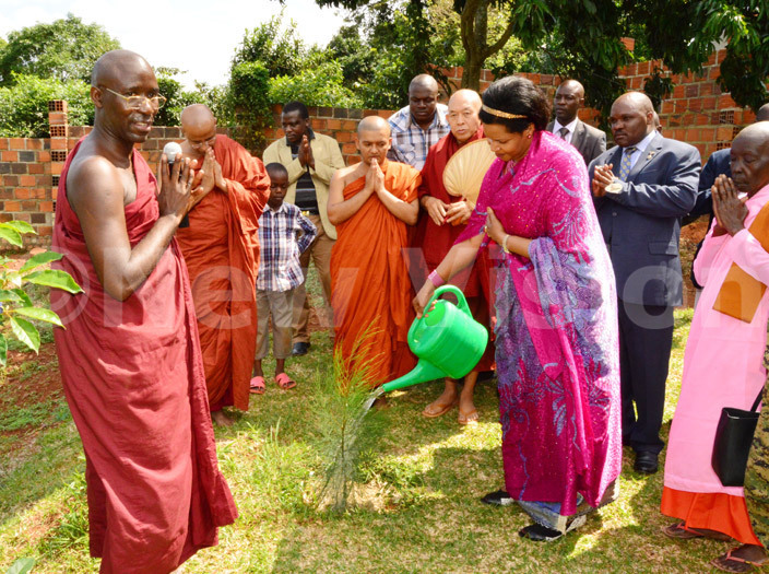 est emigisha waters a special tree she planted years back as the onks chant during the celebration of the nternational uddhist eace conference at ganda uddhist enter in ntebbe