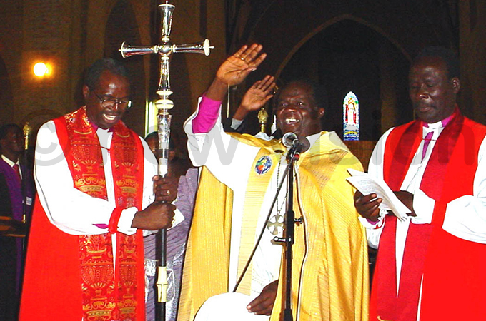 chbishop koyoyo centre bids farewell during the consecretion of his successor rchbishop enry uke rombi
