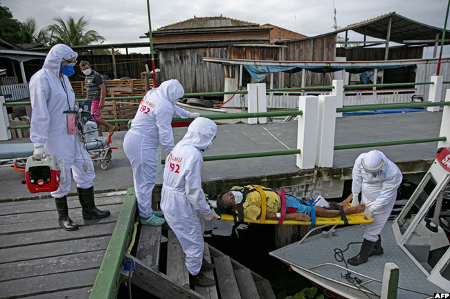 ealth personnel carry a man infected with the new coronavirus on a stretcher to be transferred on an ambulance boat from the community of ortel to a hospital in reves on arajo island ara state razil