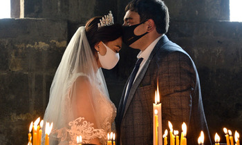 A bride and a bridegroom wearing protective face masks exchange kisses during a wedding ceremony 350x210