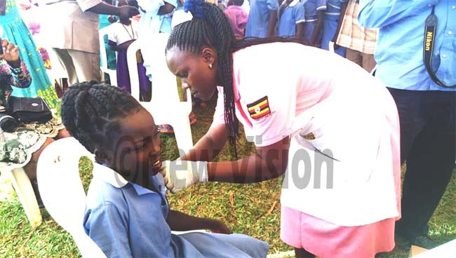 ibenda argaret left an enrolled nurse at abulungu ealth entre  immunising one of the pupils from ayuge own ouncil rimary chool while at the launch at ayuge istrict headquarter ground hoto by onald iirya