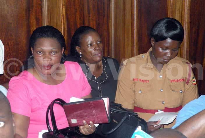 andra akungu and her sister  arah abikolo the wife to late ria ebunnya ugembe popularly known as asiwukira being guided by  prison warden at  igh  ourt ampala his was ebruary 29 2016hoto by amadhan bbey