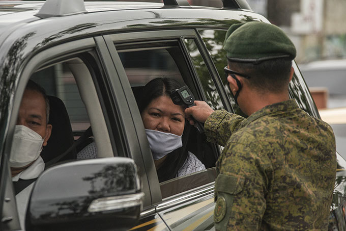 soldier checks the temperature of a car passenger at a checkpoint before entering anila on arch 16 2020 as part of measures to reduce the spread of the 19 pandemic  he virus has upended society around the planet with governments imposing restrictions rarely seen outside wartime including the closing of borders home quarantine orders and the scrapping of public events hoto