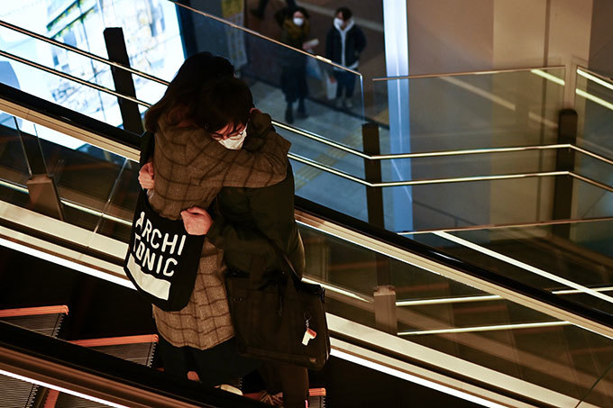 his picture taken on arch 15 2020 shows a couple embracing as they ride down an escalator in okyos hibuya area hoto