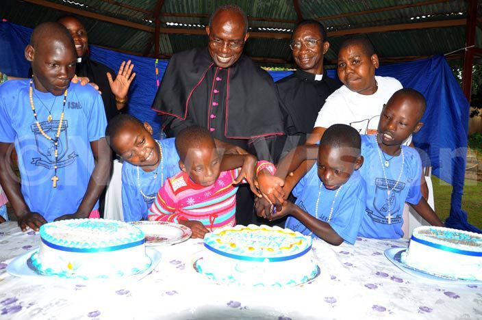 he icar general of ampala rchdiocese sgr harles asibante centre with r gnatius ivumbi parish priest amilyango parish in ugazi iocese right and  children cutting a cake during  the launch of the childrens training centre in eeta ukono district on uesday ay 3 2016 hoto by rancis morut
