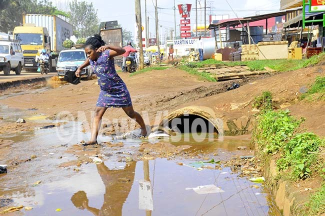lady risks her shoes in the choked drainage along   inja road highway in irekahoto by ilfred anya
