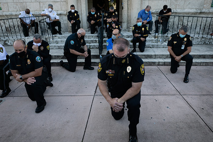 olice officers kneel during a rally in oral ables lorida on ay 30 2020 in response to the recent death of eorge loyd an unarmed black man who died while being arrested and pinned to the ground by a inneapolis police officer hoto by va arie